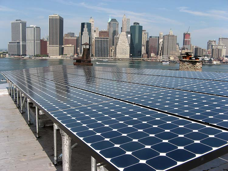 Solar photovoltaic system on a city building rooftop with skyscrapers in the background.