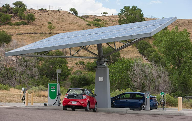 Two electric vehicles parked under a PV canopy.