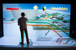 An NREL scientist works in front of a wall-sized energy system design schematic in a 3-D visualization laboratory.