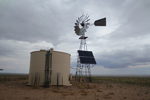 Water system holding tank and windmill with solar panels.