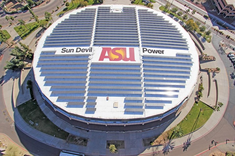 An aerial view of a sports arena with a large solar array on the roof.